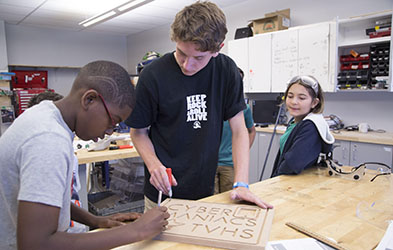 photo of three students carving letters in a block of wood.