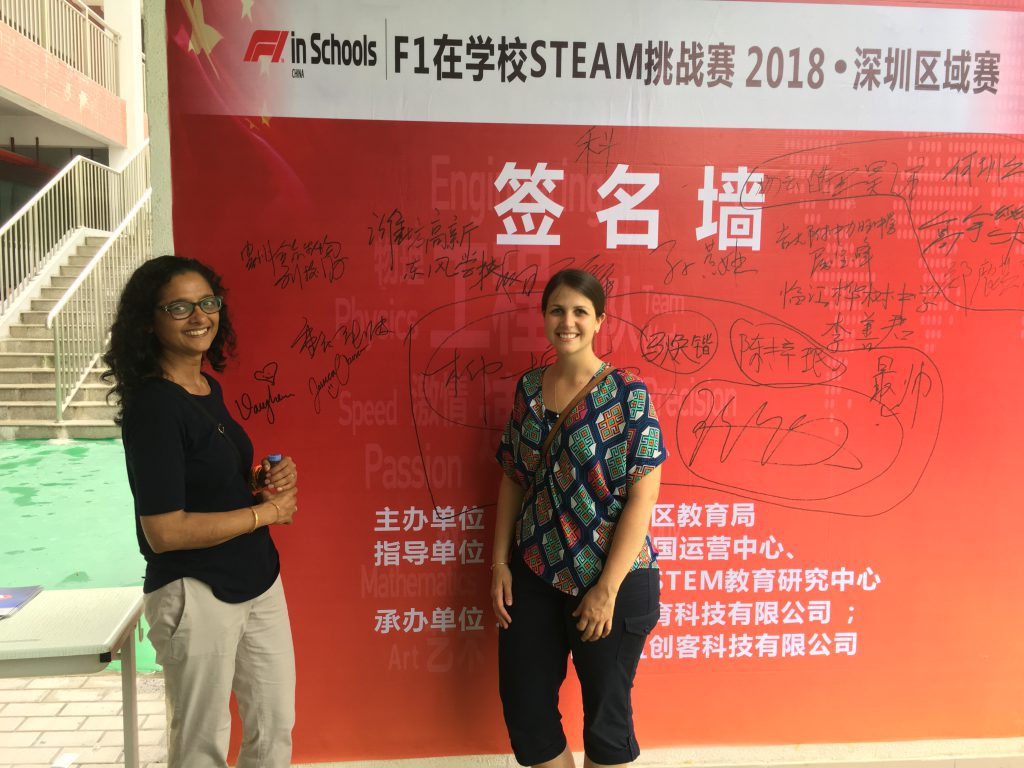 Photo of two teachers standing in front of a poster written in Chinese