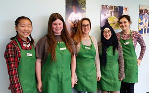 Photo of five students posing together in green aprons