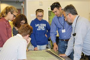 Photo of engineer reviewing a site plan with TVHS students.