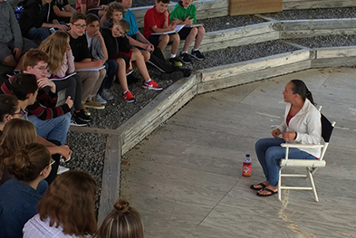 Photo of students gathered around a person telling a story.