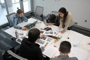 Photo of students reviewing materials at a rectangular table