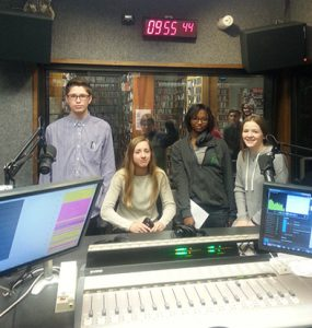 Photo of four students in a radio booth.