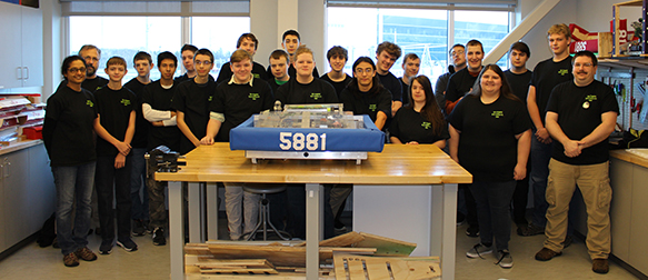 Photo of students around a table with a robot.
