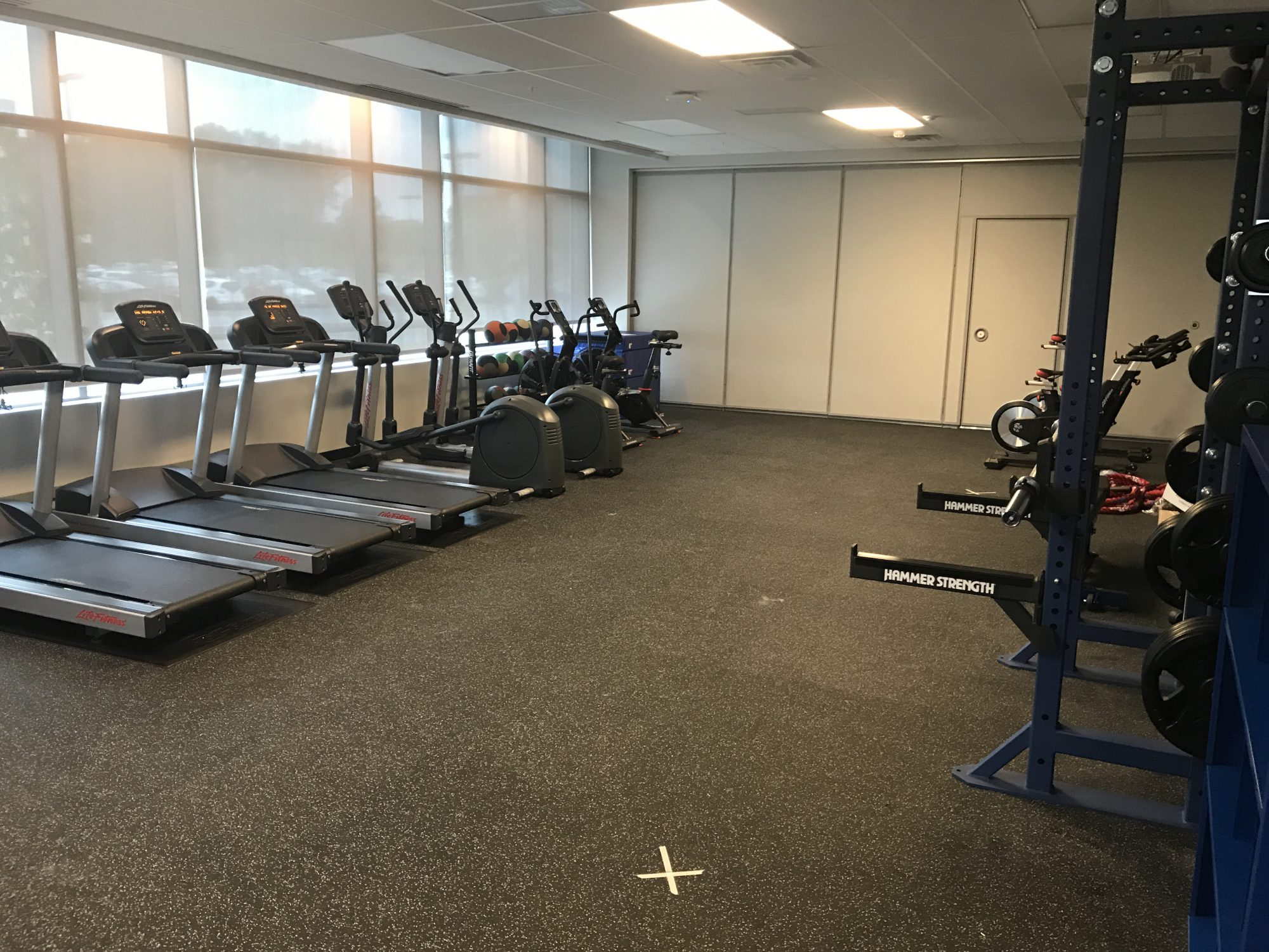 Photo of fitness center with treadmills, exercise bikes and free weights