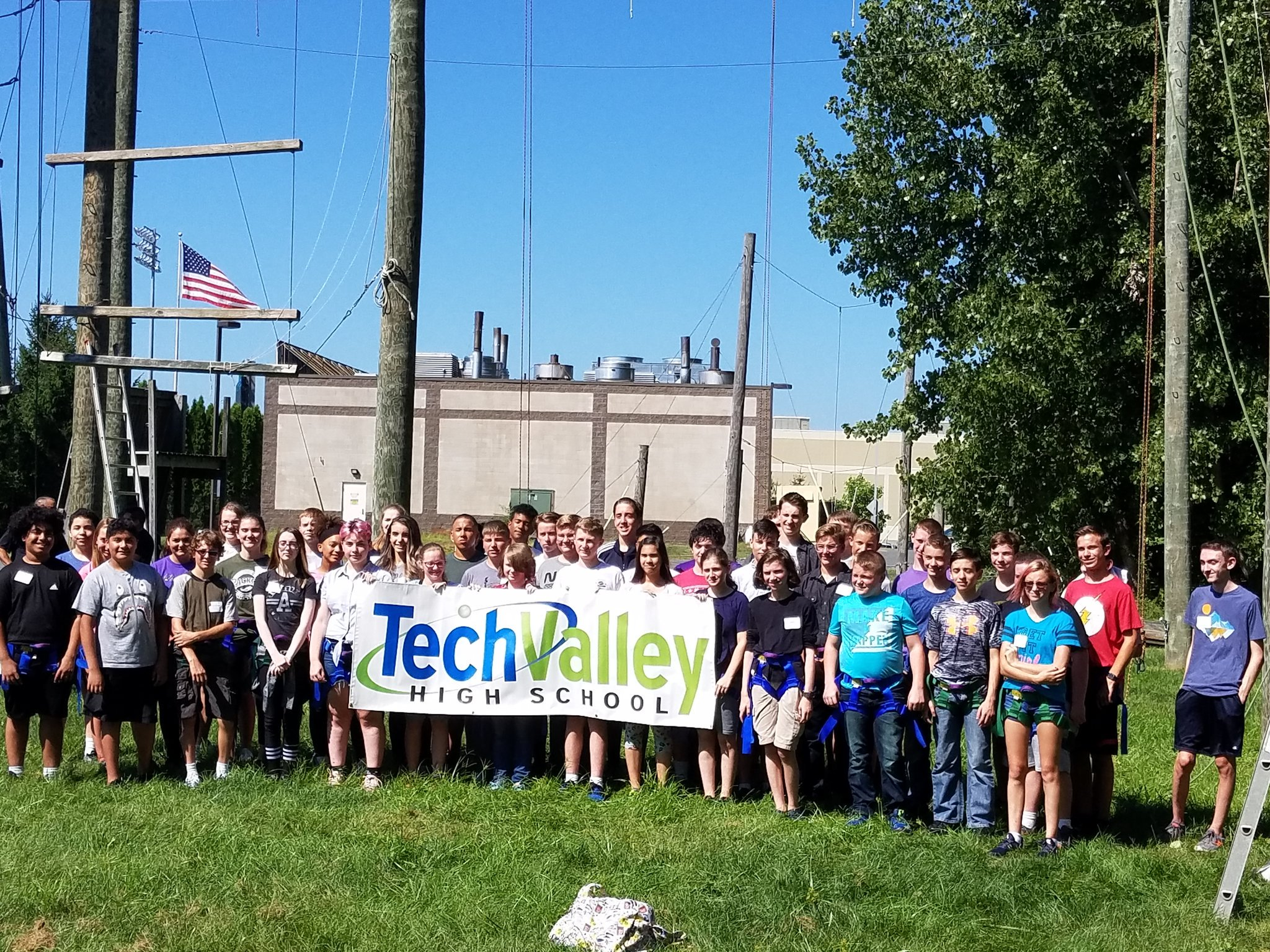 Photo of TVHS students holding banner in front of a ropes couse