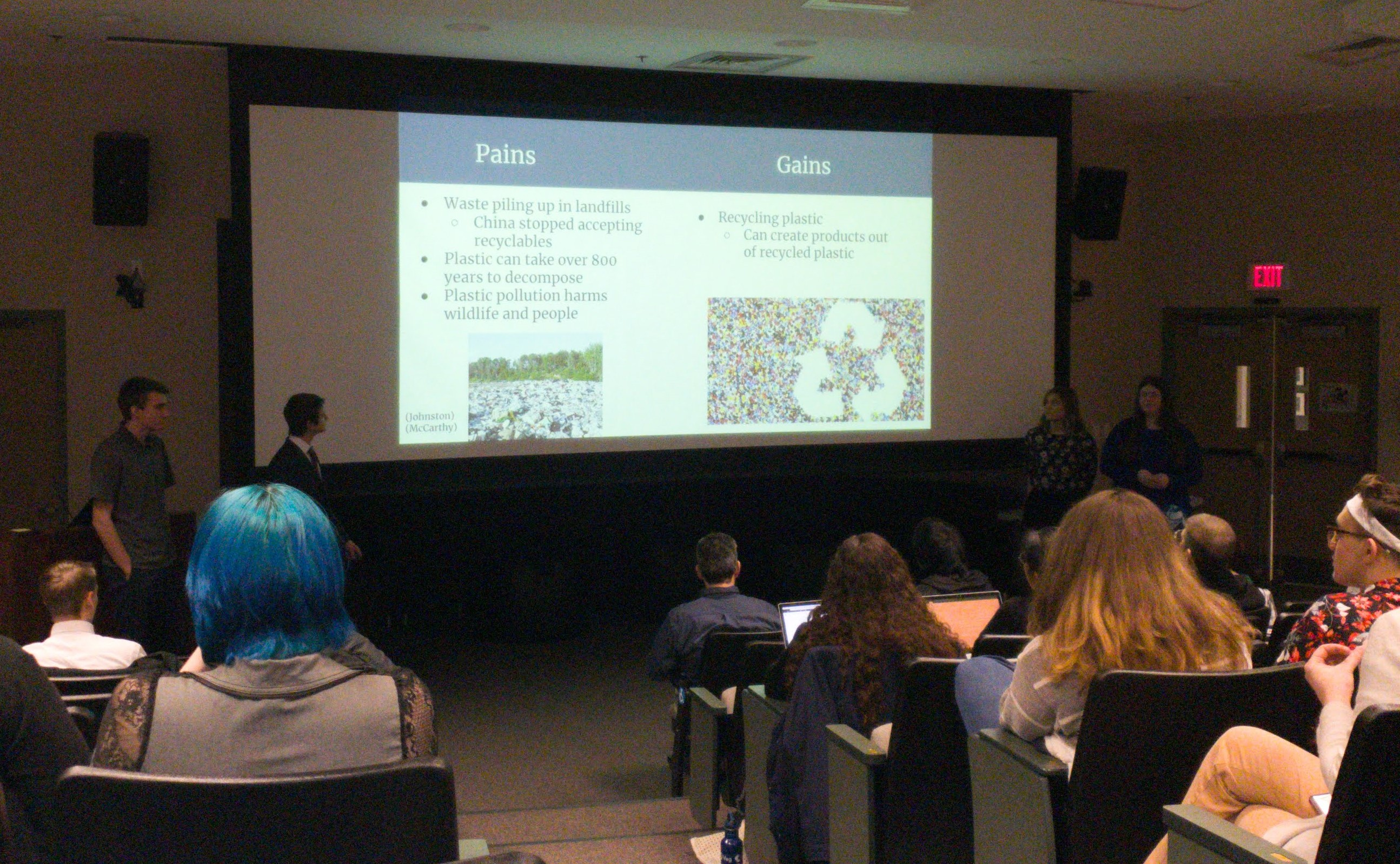 Photo of students presenting in small auditorium