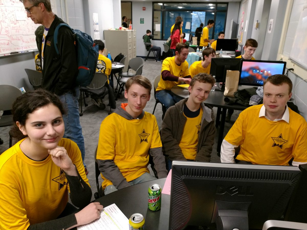 Group of students in gold shirts around a computer