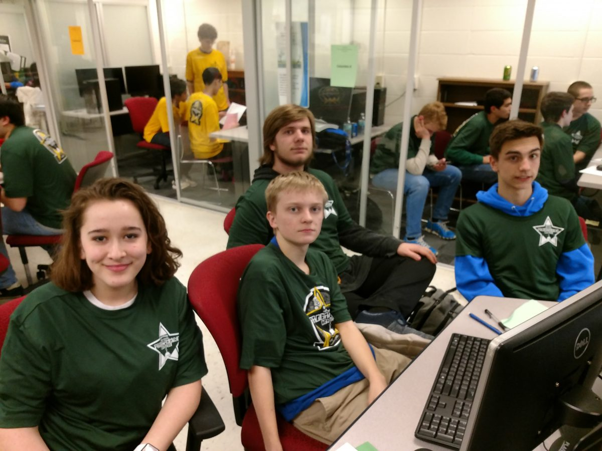 Group of students in green shirts sitting around a computer