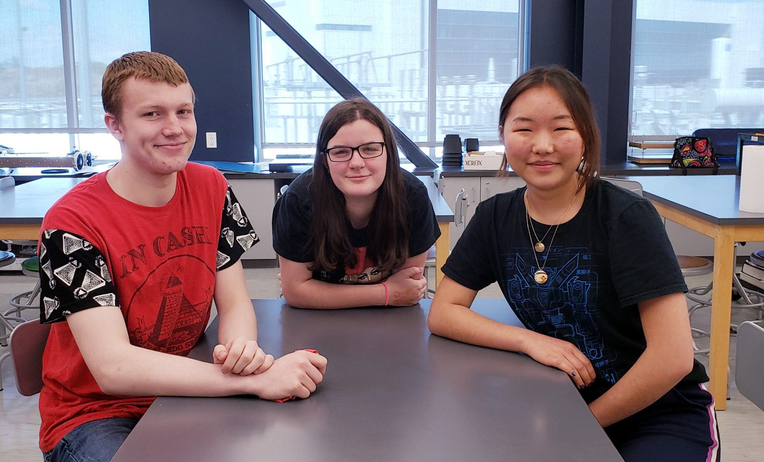 photo of three students around a table in a science classroom