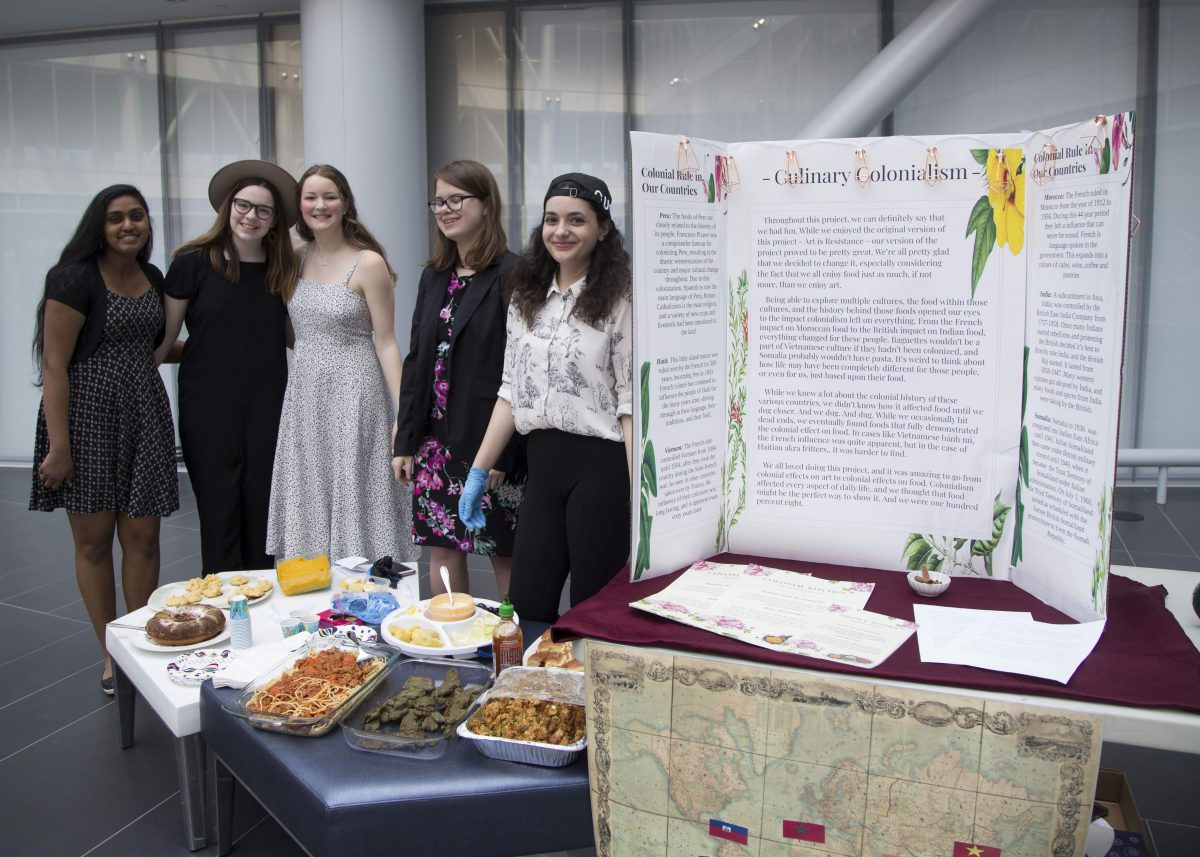 Photo of five students next to a tri-fold poster and table of food.