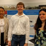 Photo of three students in front of a display board